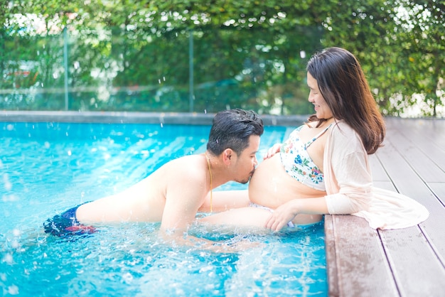 Asiatische schwangere frau mit dickem bauch. entspannen sie sich und trainieren sie mit ihrem mann im schwimmbad.