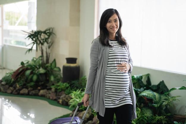 Asiatische schwangere frau stehend, die koffer zieht