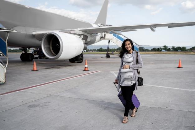 Asiatische schwangere frauen ziehen koffer, während sie auf der landebahn gehen