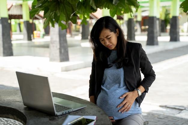 Asiatische schwangere geschäftsfrau, die anhaltenden schmerz sitzt, wenn sie mit laptop arbeitet