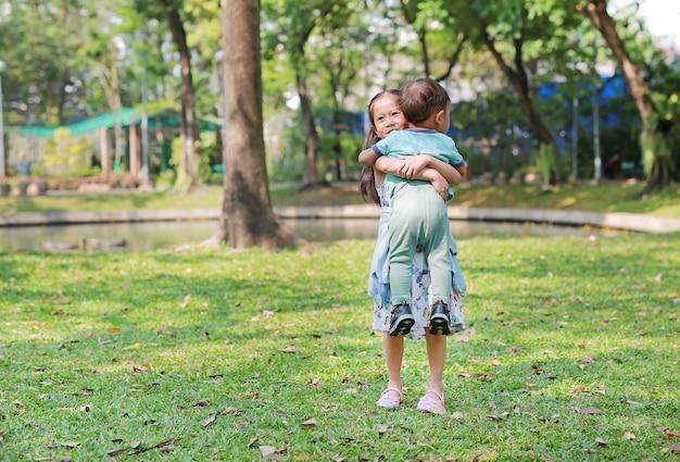 Asiatische schwester, die ihren kleinen bruder im garten im freien trägt.