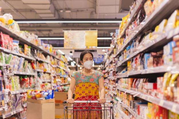 Asiatische schwester in schutzmaske, die jüngeren bruder hausaufgaben beibringt