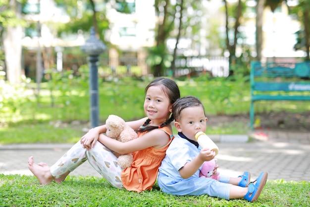 Asiatische schwester und jüngerer bruder im garten. kindermädchen-umarmungsteddybärpuppe und -junge saugen milch von der flasche.
