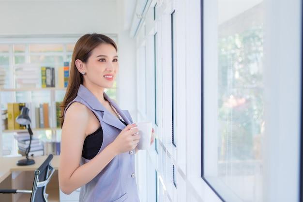 Asiatische selbstbewusste frau, die lächelt und aus dem fenster schaut, während sie eine kaffeetasse in ihren händen hält.