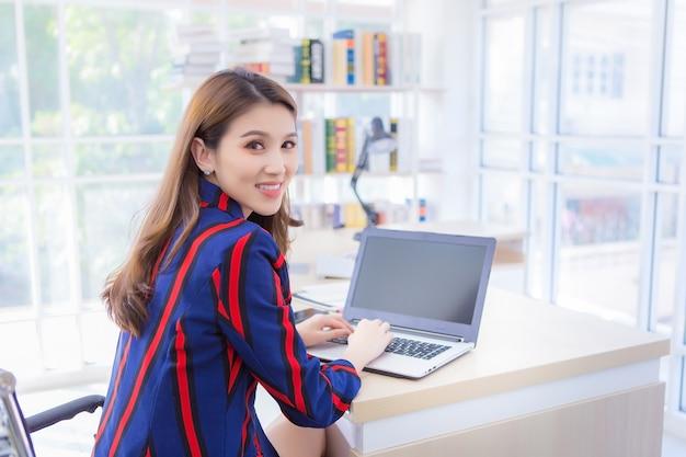 Asiatische selbstbewusste frau ruht ihre hand auf der tastatur des laptops und dreht ihr gesicht zurück