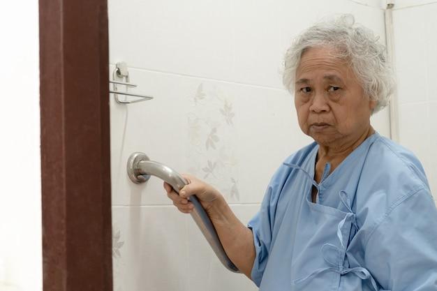 Asiatische senioren oder ältere frauenpatienten benutzen toilettenbadezimmer-griffsicherheit in der krankenstation, gesundes starkes medizinisches konzept.