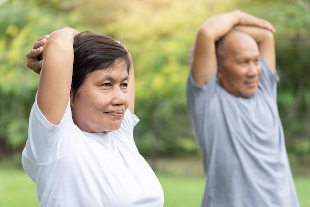 Asiatische senioren strecken ihre arme aus, bevor sie trainieren.