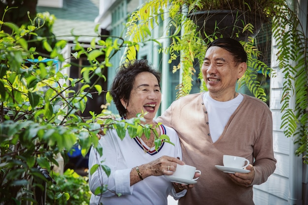 Asiatische seniorenpaare trinken tee im innenhof