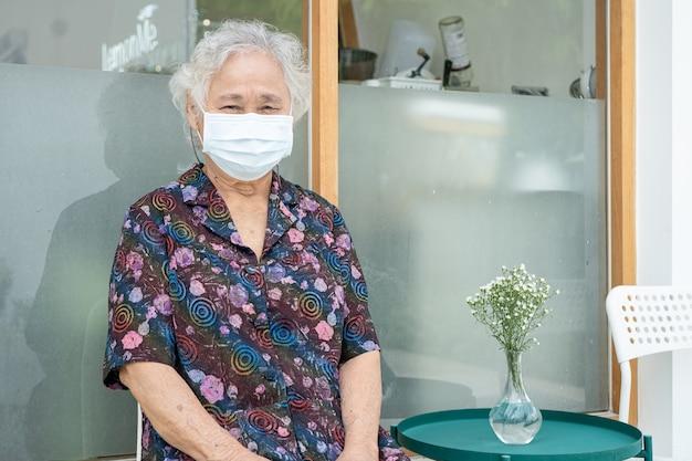 Asiatische seniorin, die im krankenhaus eine gesichtsmaske trägt, um coronavirus zu schützen