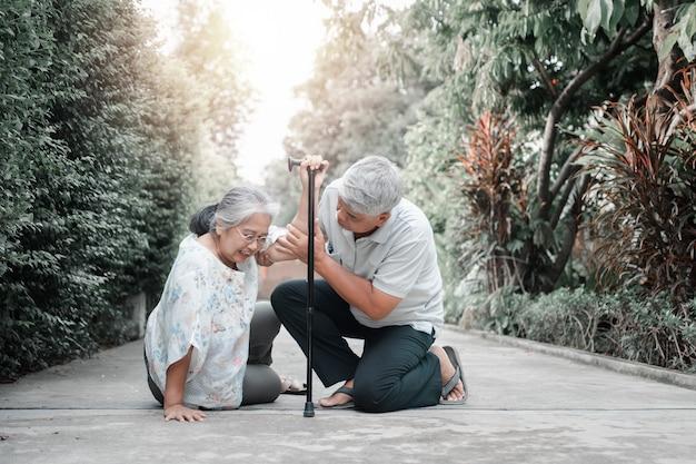 Asiatische seniorin, die zu hause auf den liegenden boden fiel, nachdem sie vor der haustür gestolpert war und vor schmerzen weinte, und ihr mann kam, um zu helfen. konzept der alten altenversicherung und des gesundheitswesens