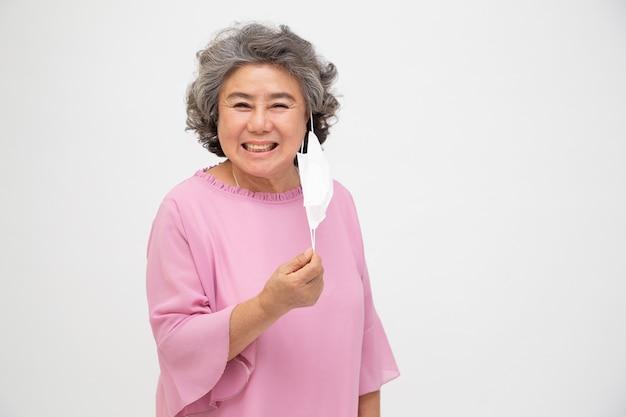 Asiatische seniorin zieht gesichtsmaske auf weißem hintergrund aus