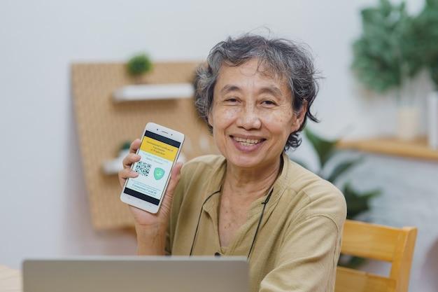 Asiatische seniorinnen, die den handybildschirm des impfstoffpasses der immunität covid19-zertifikat zeigen