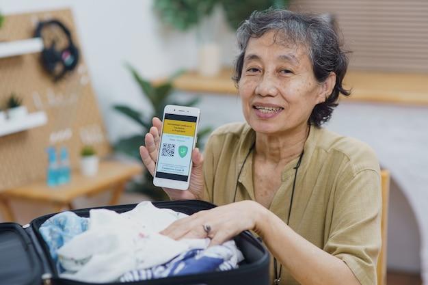 Asiatische seniorinnen, die im wohnzimmer sitzen, halten und zeigen den handybildschirm des impfstoffpasses mit dem immunitätszertifikat covid-19 zu hause. neues normales gesundheitsvisum für reisekonzept