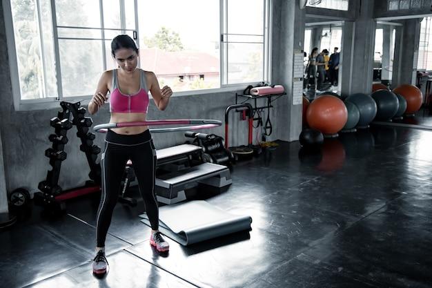 Asiatische sexy frauen trainieren mit cardio, indem sie im fitnessstudio hula hoop spielen.