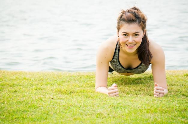 Asiatische sportfrau, die auf grüner wiese für gesundheit planking