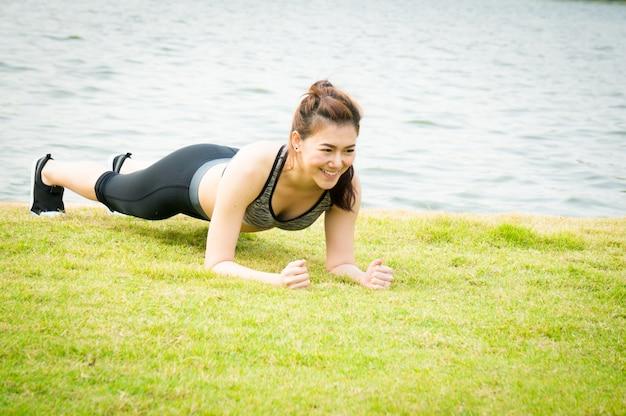 Asiatische sportfrau, die auf grüner wiese planking ist