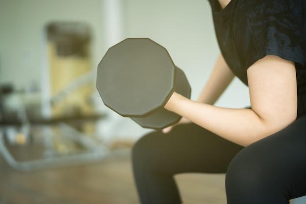 Asiatische sportfrau, die gewichtstraining mit schweren hanteln trainiert