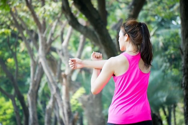 Asiatische sportfrau, die in park nachdem dem laufen ausdehnt