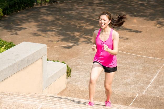 Asiatische sportfrau, die, laufend in park rüttelt