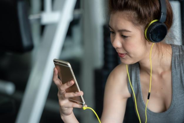 Asiatische sportfrau mit kopfhörern hörend musik für entspannen sich nach harter trainingsübung in der sportturnhalle.