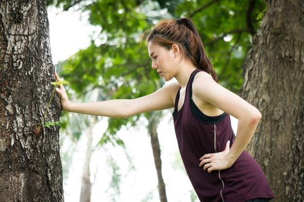 Asiatische sportfrau wird versucht und rest, nachdem sie in park gelaufen ist