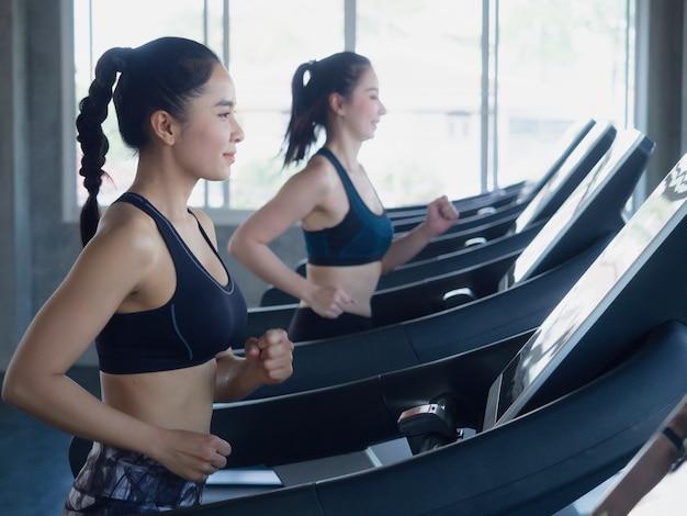 Asiatische sportfrauen auf dem laufen in turnhalle, eignungskonzept