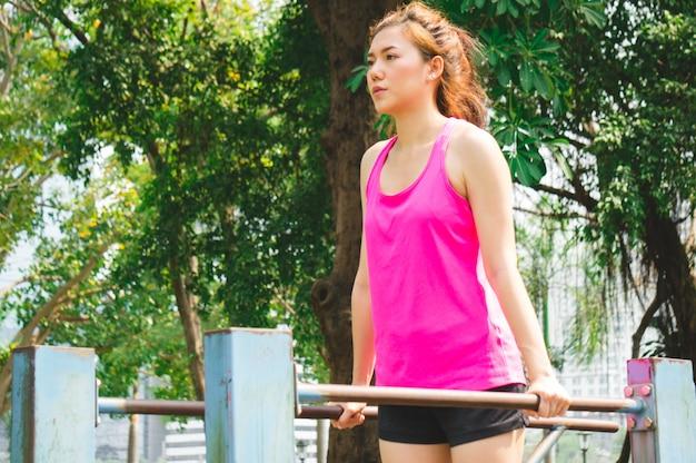 Asiatische sportfrauenübung auf stange im park