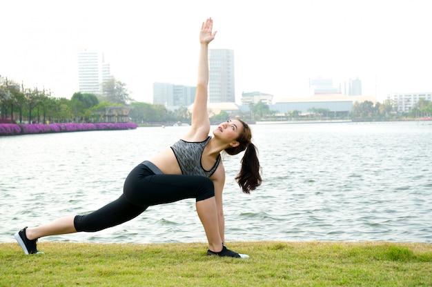 Asiatische sportfrauenübung und ausdehnen durch yoga im park