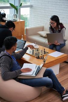 Asiatische studenten, die ihre hausaufgabe erledigen und schach spielen
