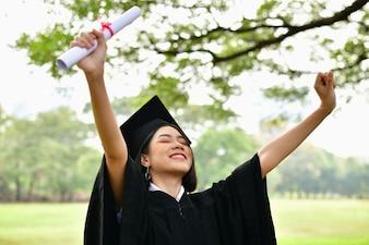 Asiatische Studenten lächeln glücklich am Abschlusstag