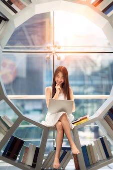Asiatische studentin las ein lehrbuch in der bibliothek ihrer universität