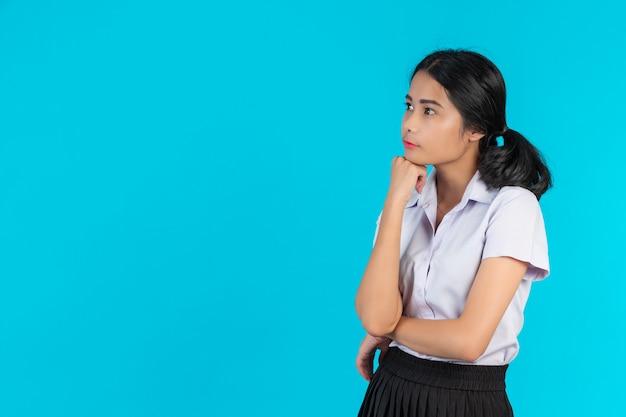 Asiatische studentinnen, die verschiedene gesten auf einem blau durchführen.