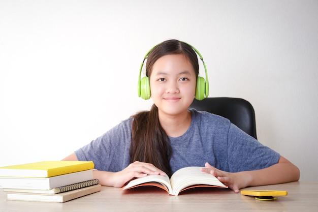 Asiatische studentinnen lernen online von zu hause aus. setzen sie kopfhörer auf und lesen sie ein buch. konzept der sozialen distanz nutzung von technologie für bildung.