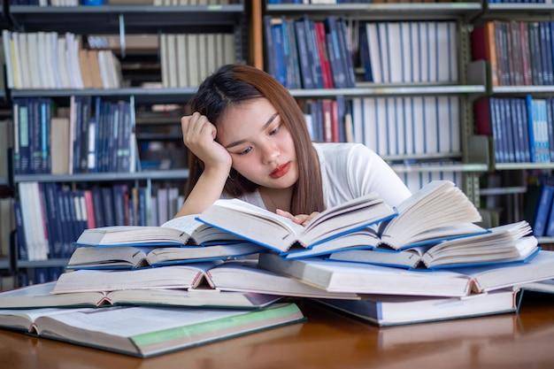 Asiatische studentinnen sind es leid, in der bibliothek zu lesen. eine studentin im teenageralter sitzt auf einem tisch mit einem stapel bücher vor sich. konzept des lesens von büchern, langeweile, prüfungsvorbereitung