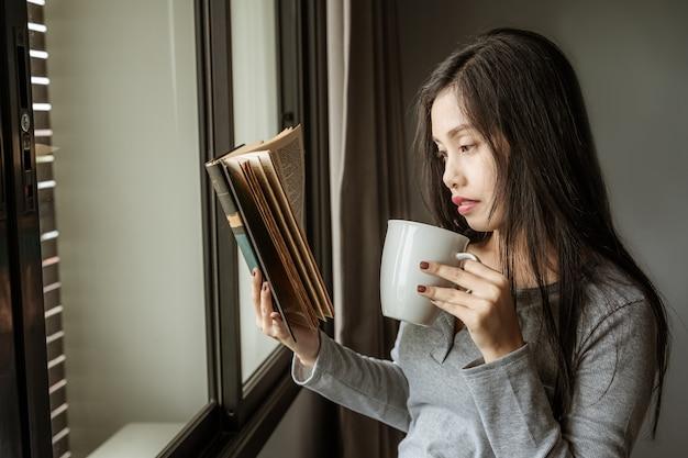 Asiatische studentinnen stehen bereit, um bücher am fenster zu lesen