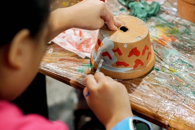 Asiatische studie des kleinen mädchens und lernen der farbe auf blumentopf im kunstklassenzimmer ihrer schule.