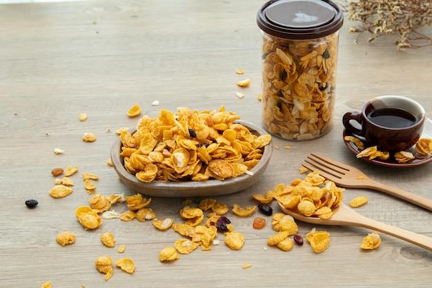 Asiatische süße snacks, leckere gemischte cornflakes, nuss, traube und karamell auf natürlichem holzhintergrund. verpackung von süßen snacks mit einer tasse tee und kopierraum. aufklebermodell für logo