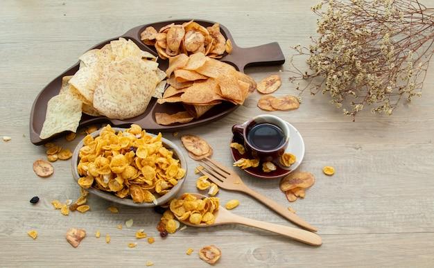 Asiatische süße und salzige snacks, leckere gemischte cornflakes, gebratene banane und gebratenes taro, nuss, traube und karamell auf natürlichem holzhintergrund. süße snacks mit einer tasse tee und textfreiraum