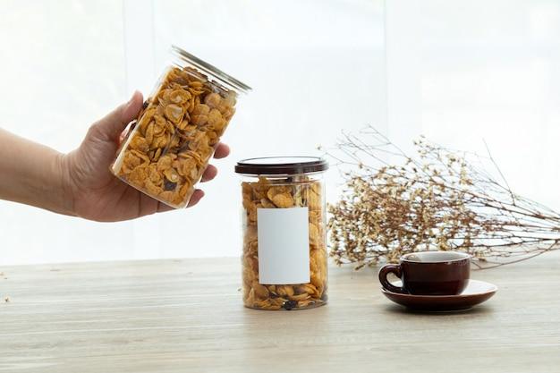 Asiatische süße und salzige snacks leckerer gemischter cornflakes-mockup-aufkleber für das logo mit einer tasse tee