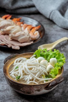 Asiatische suppe mit nudeln, schweinefleisch und frühlingszwiebeln dicht in einer schüssel auf dem tisch.