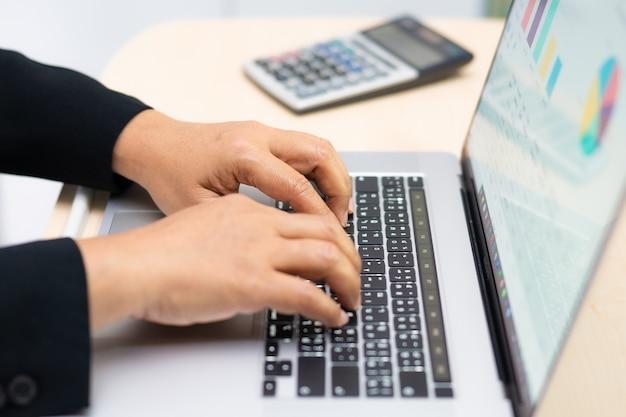 Asiatische tastatur vom typ buchhalter zur eingabe von informationen, arbeiten, berechnen und analysieren von berichtsdiagrammen projektbuchhaltung mit notizbuch in modernen büros: finanz- und geschäftskonzept.