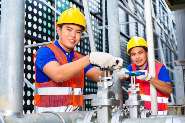 Asiatische techniker oder ingenieure, die am ventil arbeiten