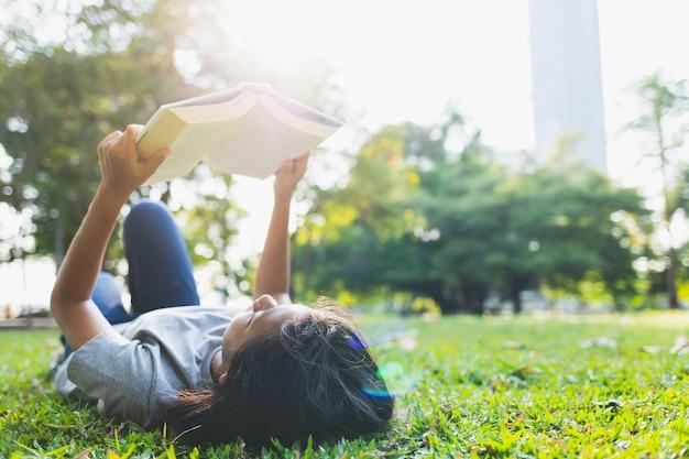 Asiatische teenager lügen lesen bücher auf dem rasen im park