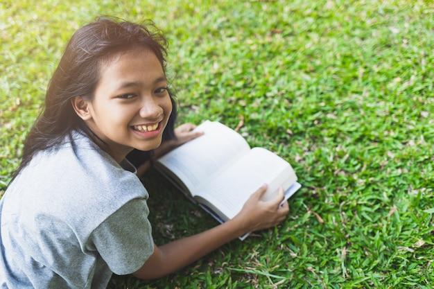 Asiatische teenager-mädchen lächeln nach dem lesen eines bücher auf dem rasen im park