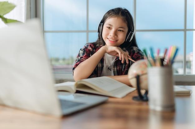 Asiatische teenager-studentin trägt drahtlose kopfhörer online mit zoom-meeting, glückliche junge frau lernt sprache hören vorlesung webinar ansehen notizen schreiben blick auf laptop-fernbildung.