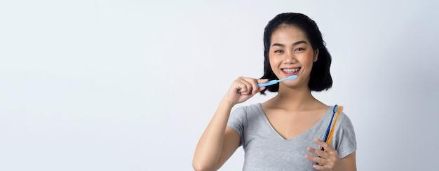 Asiatische teenie-gesichtsbehandlung mit zahnspange und lächeln in die kamera, um kieferorthopädische zähne zu zeigen, die pr . enthalten