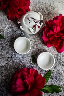 Asiatische teezeremonie verziert mit roten pfingstrosenblumen