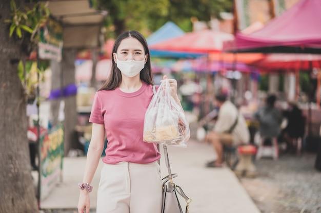 Asiatische thailänderinnen verwenden gesichtsmaskeneinkäufe auf dem straßenmarkt, nachdem der corona-virus freigeschaltet wurde