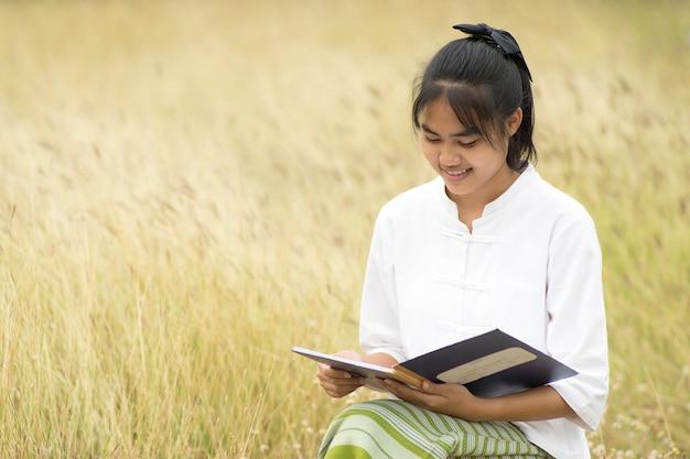 Asiatische thailändische frau, die ein buch am wiesenfeld sitzt und liest.