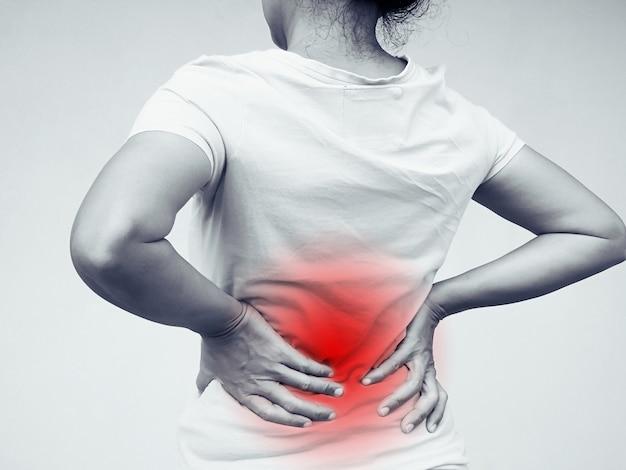 Asiatische thailändische frauen, die unter rückenschmerzen und lendenschmerzen am körper leiden.